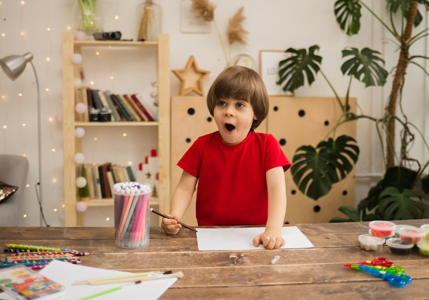 Surprised little boy draws with a colored felt-tip pen on white paper at a wooden desk with stationery in the room