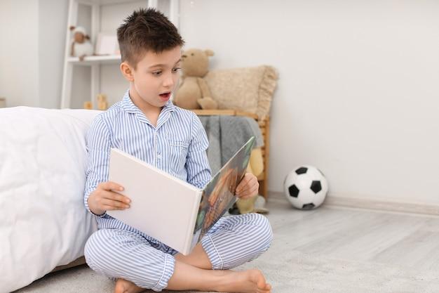 Удивленный маленький мальчик читает сказку на ночь дома