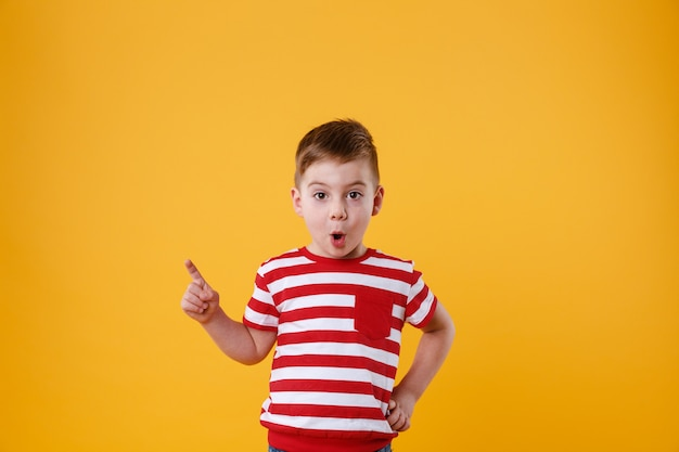 Surprised little boy standing and pointing finger away