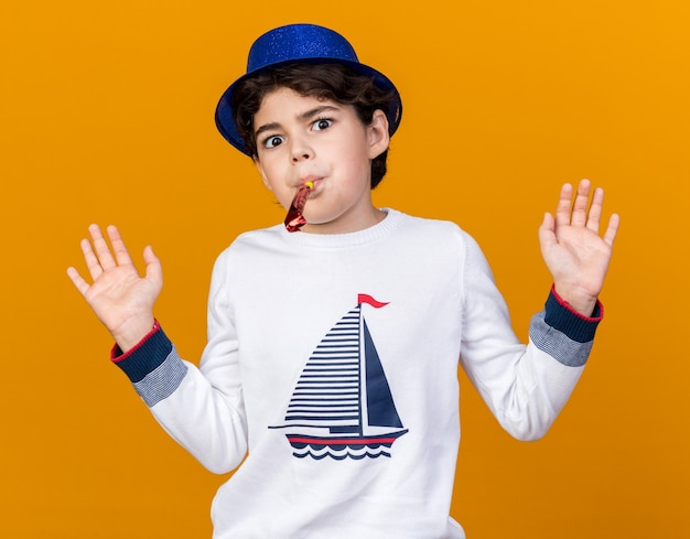 Surprised little boy wearing blue party hat blowing party whistle spreading hands isolated on orange wall