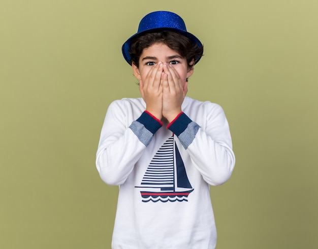 青いパーティーハットを身に着けている驚いた少年は、オリーブグリーンの壁に隔離された手で顔を覆った