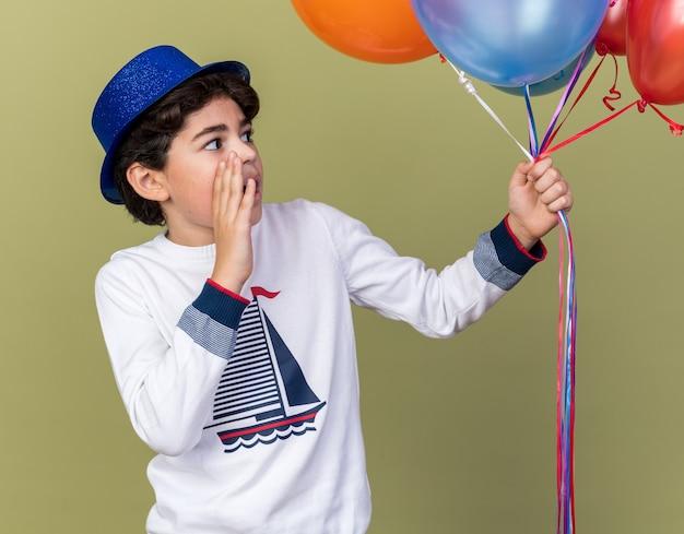 파란색 파티 모자를 쓰고 올리브 녹색 벽에 고립된 사람을 부르는 풍선을 보고 놀란 어린 소년