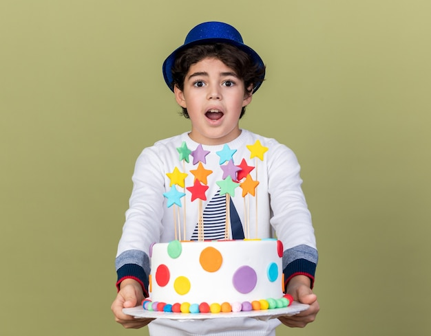 Surprised little boy wearing blue party hat holding out cake at camera
