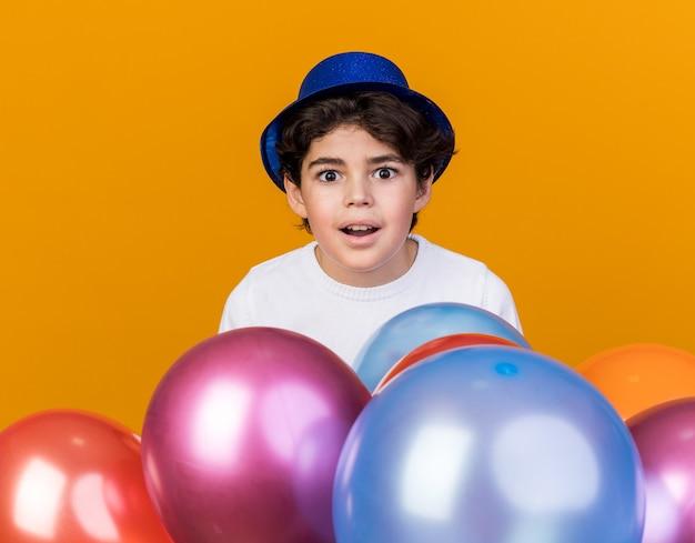Удивленный маленький мальчик в синей партийной шляпе, стоящий за воздушными шарами, изолированными на оранжевой стене