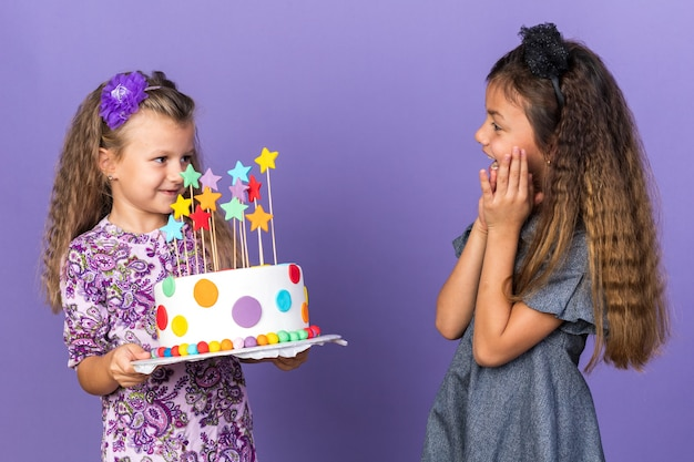 コピースペースで紫色の壁に分離されたバースデーケーキを保持している喜んでいる小さなブロンドの女の子を見て驚いた小さな白人の女の子