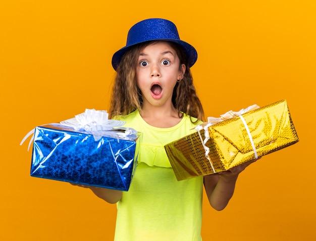 Piccola ragazza caucasica sorpresa con cappello da festa blu che tiene scatole regalo isolate sulla parete arancione con spazio copia