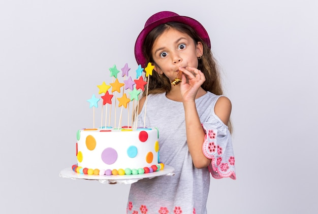 Surprised little caucasian girl with purple party hat holding birthday cake and blowing party whistle isolated on white wall with copy space