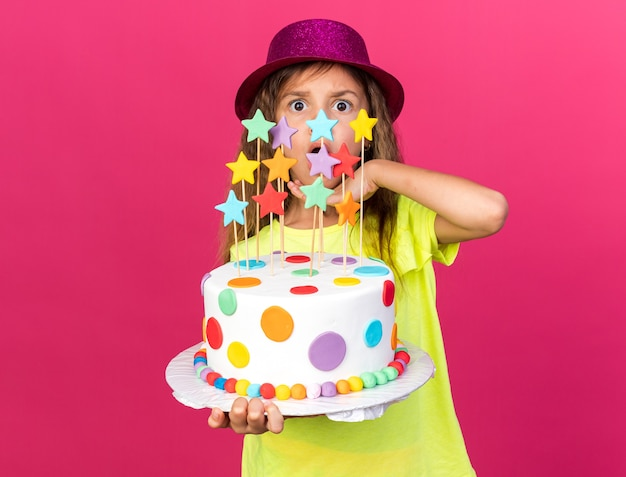 Surprised little caucasian girl with purple party hat holding birthday cake and putting hand on chin isolated on pink wall with copy space