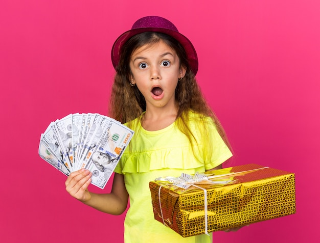 Piccola ragazza caucasica sorpresa con cappello da festa viola che tiene scatola regalo e denaro isolato sulla parete rosa con spazio per la copia