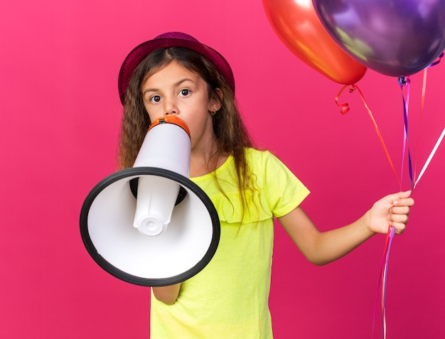 Surprised little caucasian girl with purple party hat holding helium balloons and loud speaker isolated on pink wall with copy space