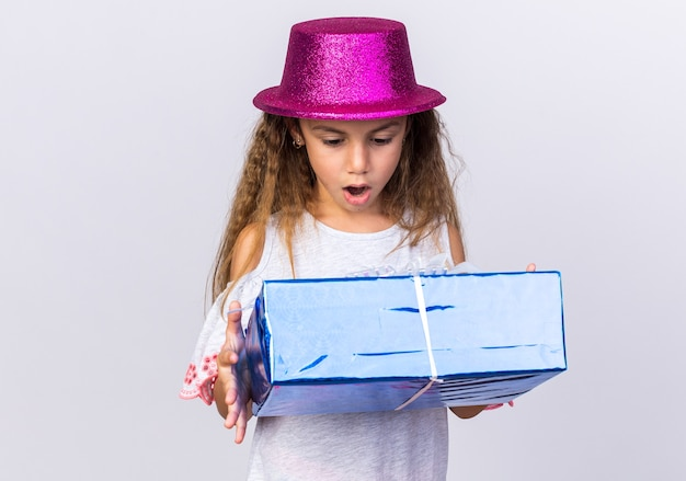 Surprised little caucasian girl with purple party hat holding and looking at gift box isolated on white wall with copy space
