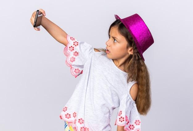 Piccola ragazza caucasica sorpresa con il cappello viola del partito che esamina il telefono che prende selfie isolato sulla parete bianca con lo spazio della copia