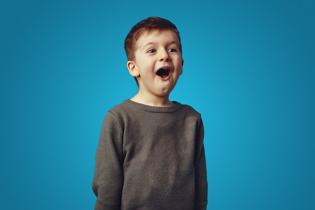 Удивленный маленький милый мальчик, кричащий omg, изолированный на синем фоне
