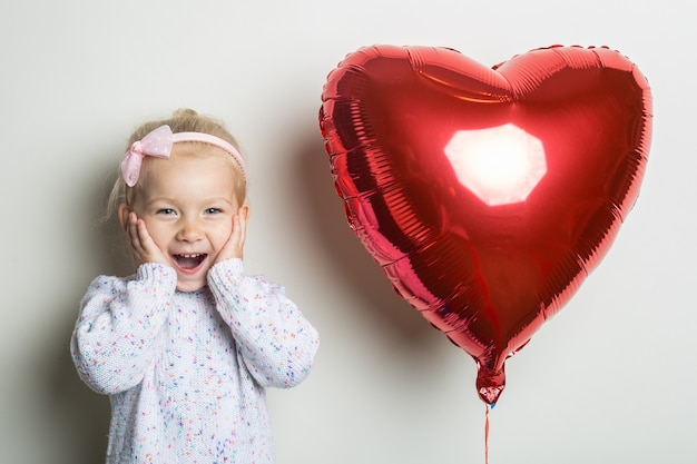Surprised little girl and heart air balloon on a light background. concept for valentine's day, birthday. banner.