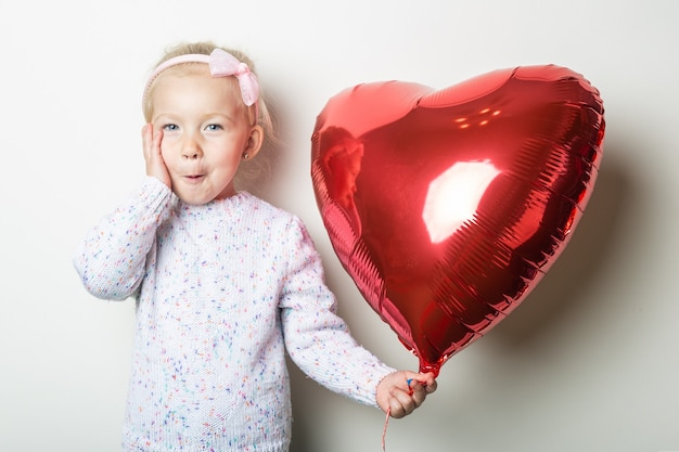 Surprised little girl holding a heart air balloon on a light background. concept for valentine's day, birthday. banner.