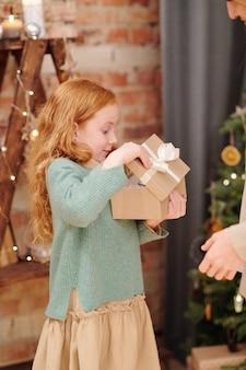 彼女の母親からのクリスマスプレゼントでギフトボックスを開くカジュアルウェアで驚いた少女
