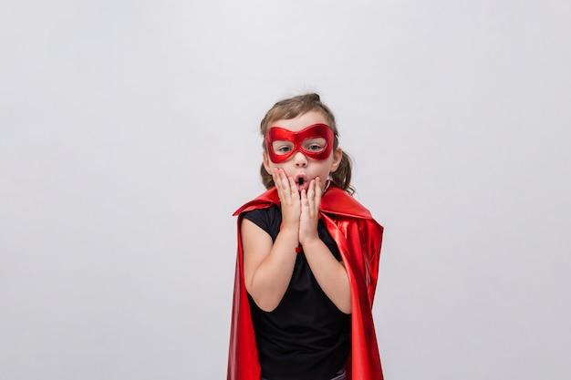 Удивленная маленькая девочка в костюме супергероя