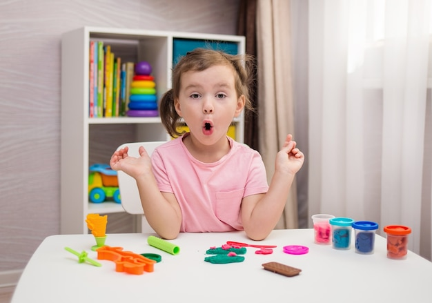 A surprised little girl is playing play-doh at a table in the children's room