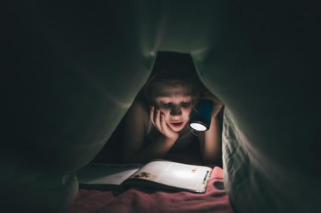 Удивленная маленькая девочка читает книгу под одеялом с фонариком в темной комнате ночью, в постели, тонна