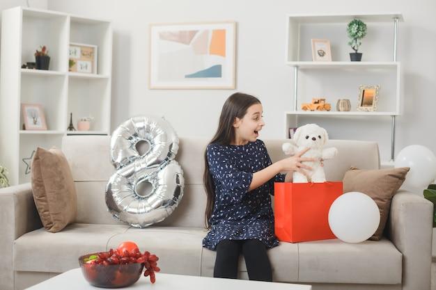 Удивленная маленькая девочка в счастливый женский день держит и смотрит на плюшевого мишку, сидящего на диване в гостиной