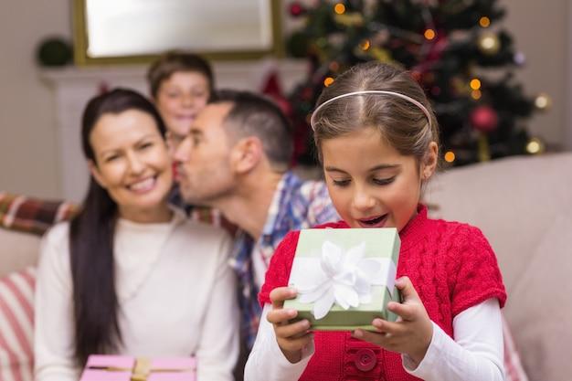 驚いた小さな女の子が贈り物を開く