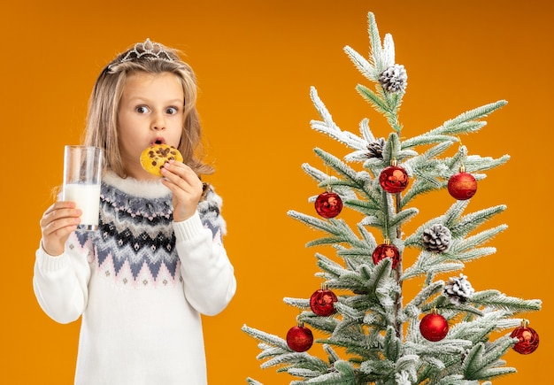 Surprised little girl standing nearby christmas tree wearing tiara with garland on neck holding glass of milk trying cookies isolated on orange background