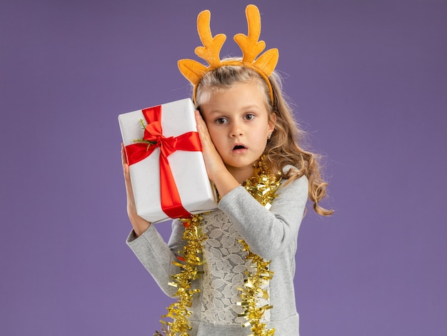 Surprised little girl wearing christmas hair hoop with garland on neck holding gift box around face isolated on blue wall