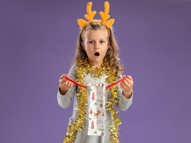 青い背景で隔離のギフトバッグを保持している首に花輪とクリスマスの髪のフープを身に着けている驚きの少女