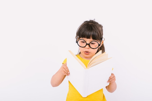 Удивленная маленькая девочка в желтой футболке и круглых черных очках держит в руках открытую книгу и читает на белом фоне