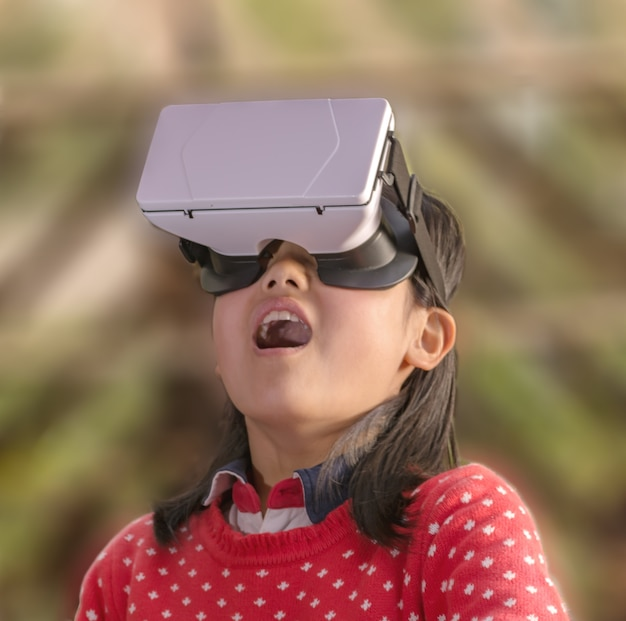 Surprised little girl with a virtual glasses