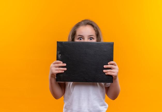 Удивленная маленькая школьница в белой футболке прикрыла рот с буфером обмена на изолированном оранжевом фоне
