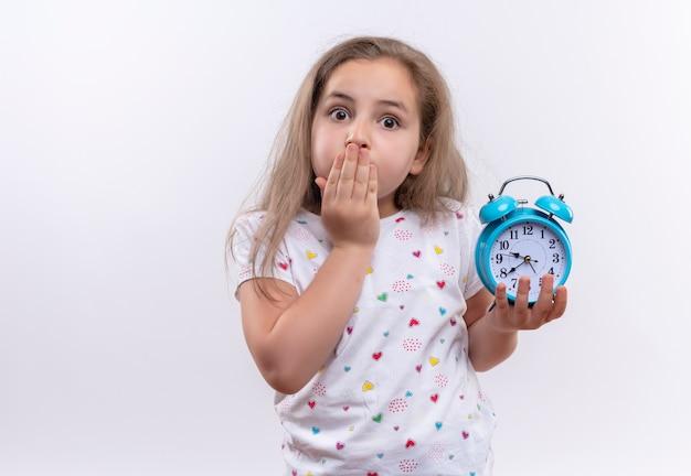 알람 시계를 들고 흰색 티셔츠를 입고 놀란 어린 학교 소녀 격리 된 흰색 배경에 입 덮여