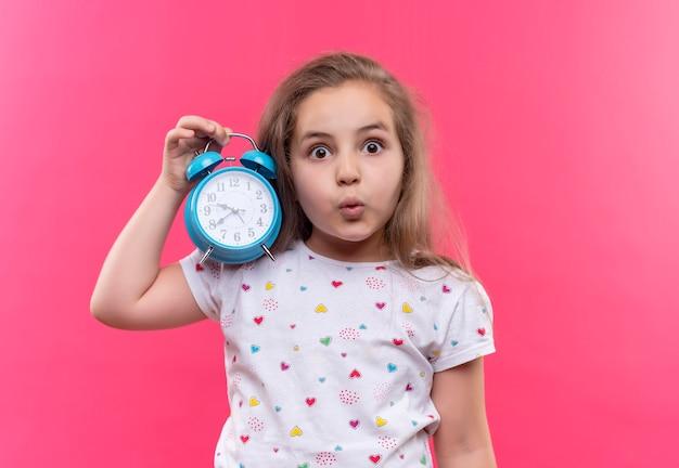 Удивленная маленькая школьница в белой футболке с будильником на изолированном розовом фоне