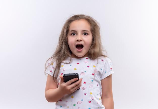 격리 된 흰색 배경에 전화 오픈 입을 들고 흰색 티셔츠를 입고 놀란 어린 학교 소녀