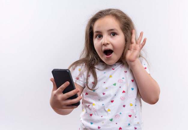 Surprised little school girl wearing white t-shirt holding phone showing listen gesture on isolated white background