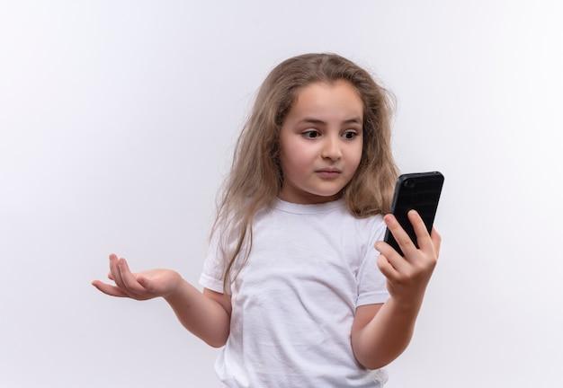 孤立した白い背景の上の電話で見て白いtシャツを着て驚いた小さな女子高生