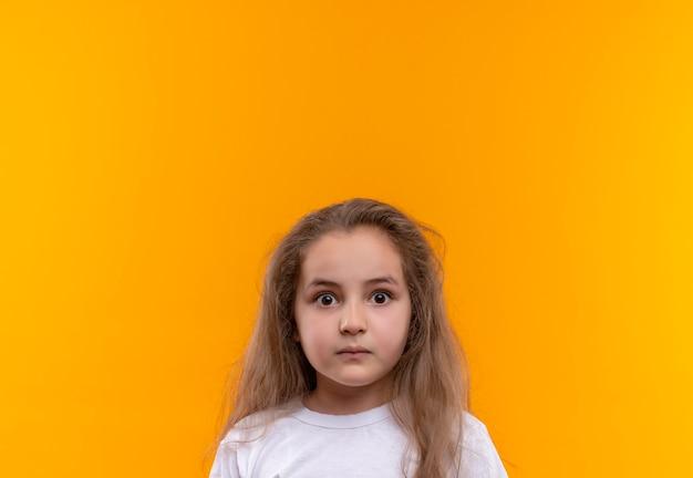 孤立したオレンジ色の背景に白いtシャツを着て驚いた小さな女子高生