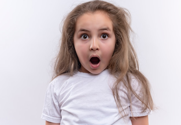 La piccola maglietta bianca da portare sorpresa della ragazza della scuola ha aperto la bocca su fondo bianco isolato