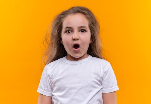 격리 된 오렌지 배경에 흰색 티셔츠 여는 입을 입고 놀란 어린 여고생