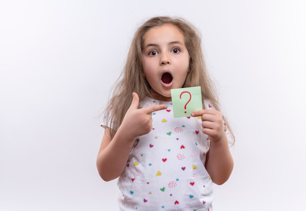 Surprised little school girl wearing white t-shirt points to paper question mark on isolated white background