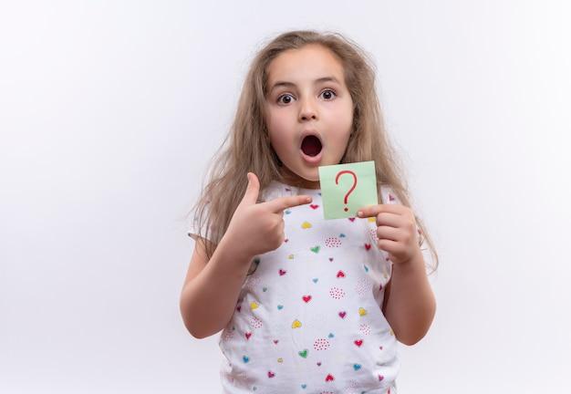 白いtシャツを着て驚いた小さな女子高生は、孤立した白い背景の上の紙の疑問符を指しています