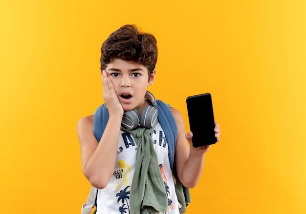 Piccolo scolaro sorpreso che indossa la borsa posteriore e le cuffie che tengono il telefono e che mette la mano sulla guancia isolata su colore giallo