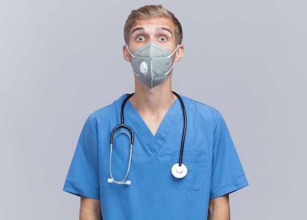 흰색 벽에 고립 된 청진 기 및 의료 마스크와 의사 유니폼을 입고 카메라 젊은 남성 의사를보고 놀란