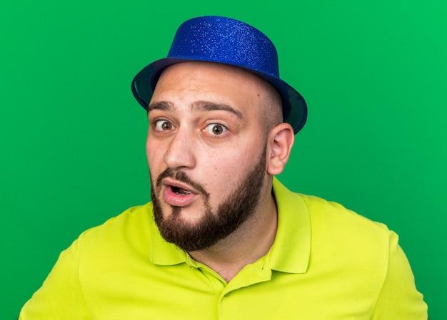 파란색 파티 모자를 쓰고 카메라 젊은 남자를 보고 놀란
