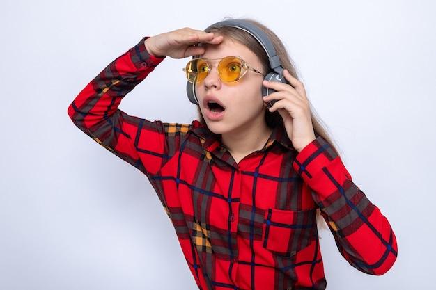 빨간 셔츠와 헤드폰을 끼고 안경을 쓴 아름다운 어린 소녀가 손으로 거리를 보고 놀란다