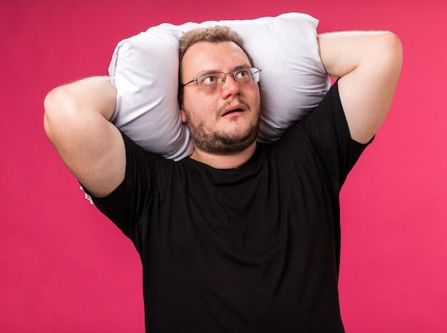 분홍색 벽에 격리된 머리 뒤에 베개를 들고 있는 중년의 아픈 남성을 보고 놀란다