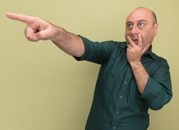 올리브 녹색 벽에 고립 된 입에 손을 넣어 측면에서 녹색 티셔츠 포인트를 입고 측면 중년 남자를보고 놀란