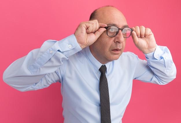 넥타이와 분홍색 벽에 고립 된 안경 흰색 티셔츠를 입고 측면 중년 남자를보고 놀란
