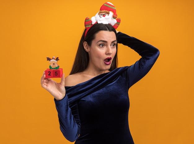 青いドレスとオレンジ色の背景で隔離の頭の後ろに手を置いておもちゃを保持しているクリスマスの髪のフープを身に着けている側の若い美しい少女を見て驚いた