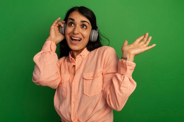 Удивленная, глядя на сторону молодой красивой девушки в розовой футболке с наушниками, протягивая руку, изолированную на зеленой стене